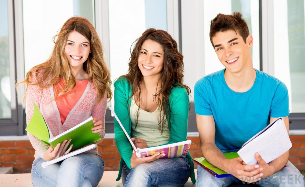 2474_two-girls-and-one-boy-student-smiling-with-notebooks.jpg